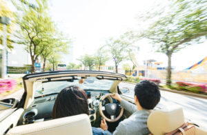 男女がオープンカーでドライブしている様子の画像